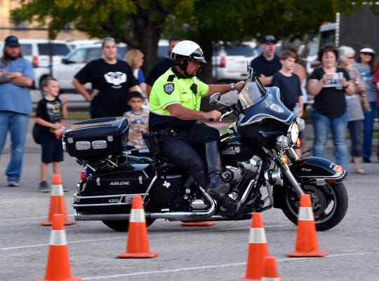 Abilene Police Department motorcycle officer Tyson Kropp rides sidesaddle while weaving through an obstacle course during Tuesday's National Night Out at the Abilene/Taylor County Law Enforcement Center.