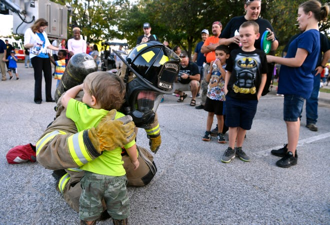 Brent Holsenbeck, an Abilene Fire Department firefighter with Station 1, gets an appreciative hug from a young fan during the National Night Out on Tuesday. This was the last such event held at the Abilene/Taylor County Law Enforcement Center. By this time next year the Abilene Police Department expects to be at its new location on South First Street in the former Kmart shopping center.