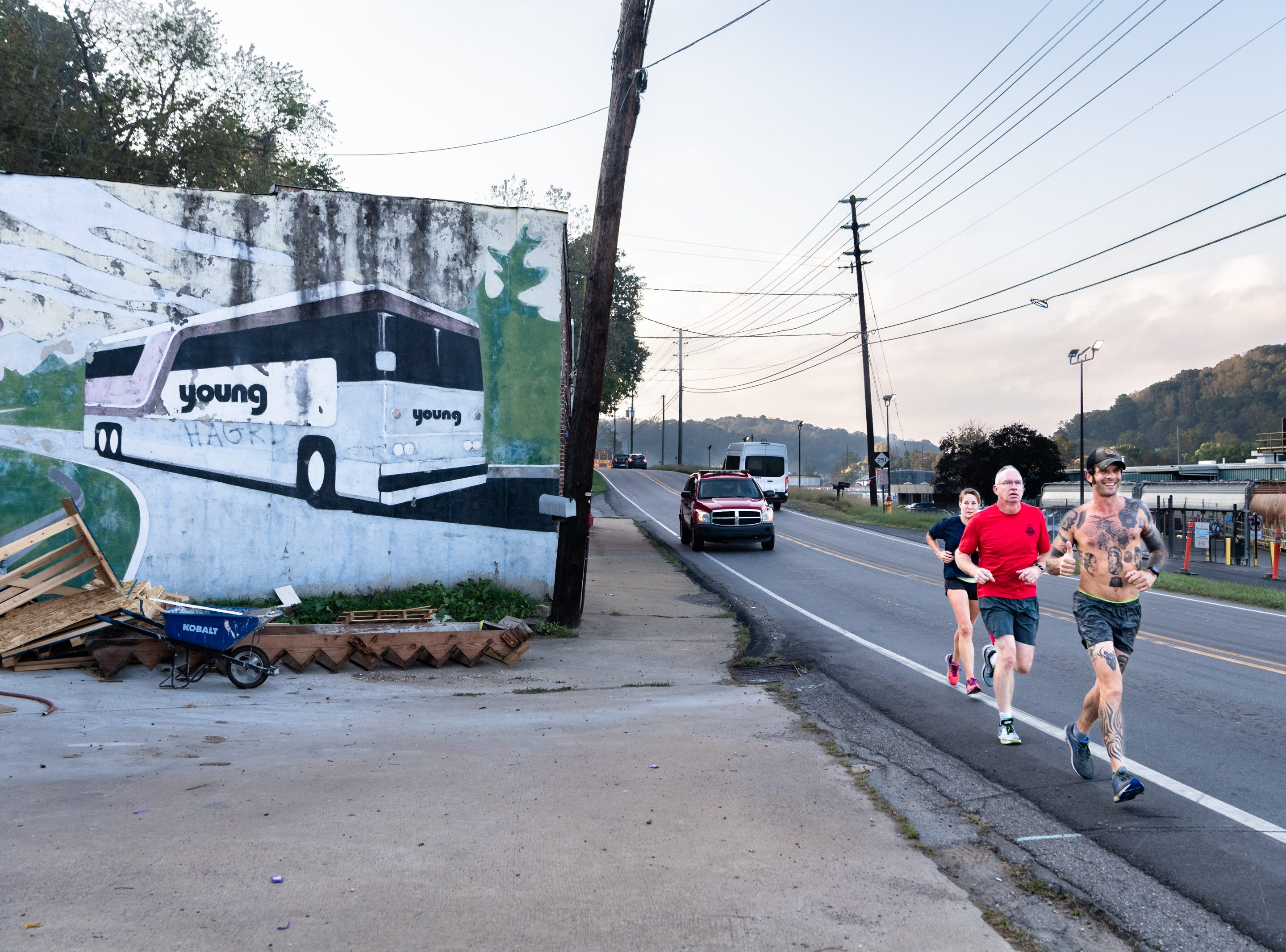 Mikey Riley, an Asheville firefighter, runs down Riverside Drive with Captain Steve Wickam and Angela Wyricks at the beginning of his 100k to Ebbs Chapel and back Oct. 8, 2018. Riley is running one mile for every firefighter who has ever been diagnosed with cancer in an effort to raise awareness of firefighters' higher risk of cancer than the general population.