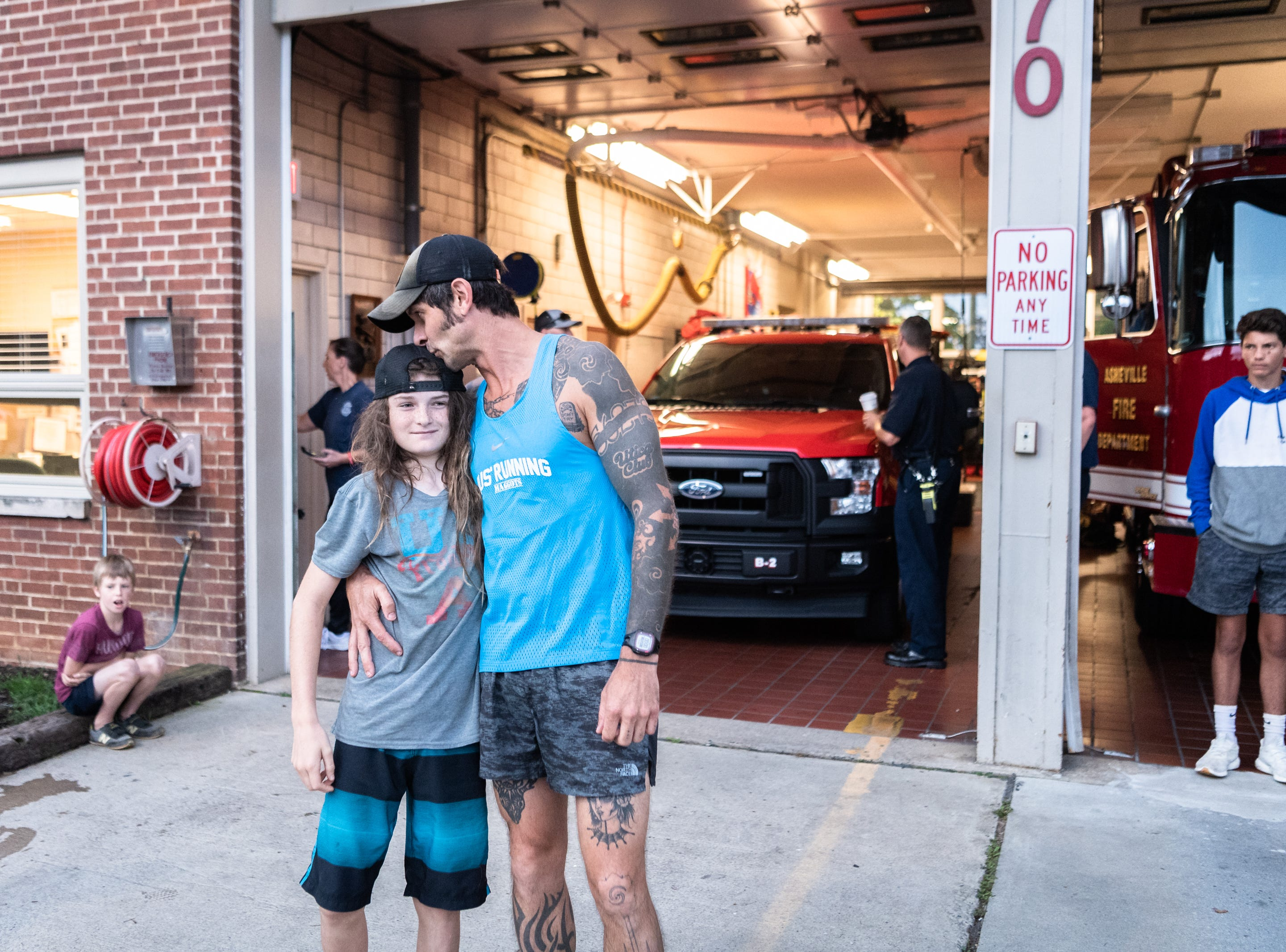 Mikey Riley, an Asheville firefighter, kisses his son Cadence at station 6 on Haywood Road before beginning his 100k run to Ebbs Chapel and back, Oct. 8, 2018. Riley is running one mile for every firefighter who has ever been diagnosed with cancer in an effort to raise awareness of firefighters' higher risk of cancer than the general population and expects to arrive back around 7 P.M.