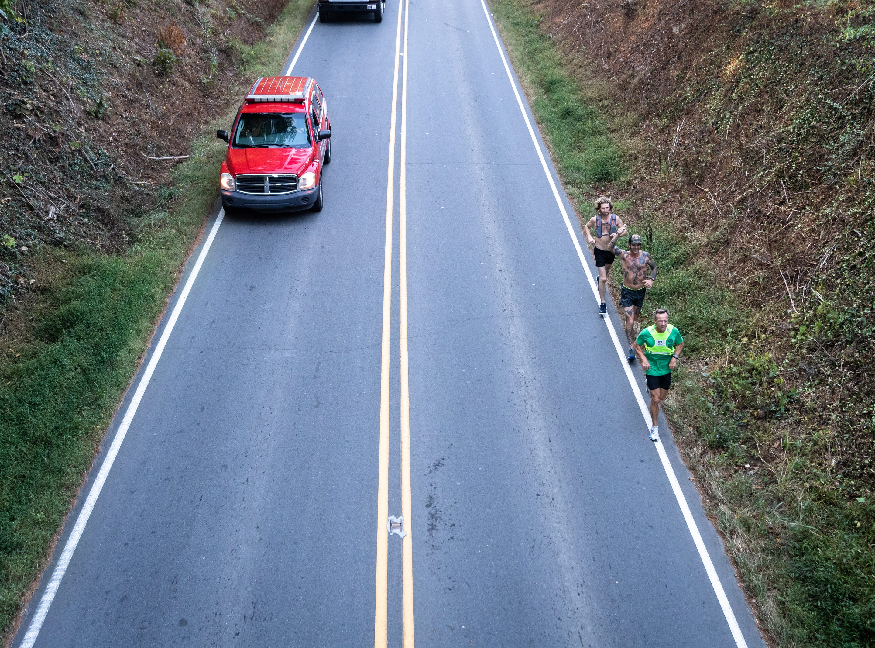 Mikey Riley, an Asheville firefighter, in center, runs down Merrimon Avenue in Weaverville at the beginning of his 100k to Ebbs Chapel and back Oct. 8, 2018. Riley is running one mile for every firefighter who has ever been diagnosed with cancer in an effort to raise awareness of firefighters' higher risk of cancer than the general population.