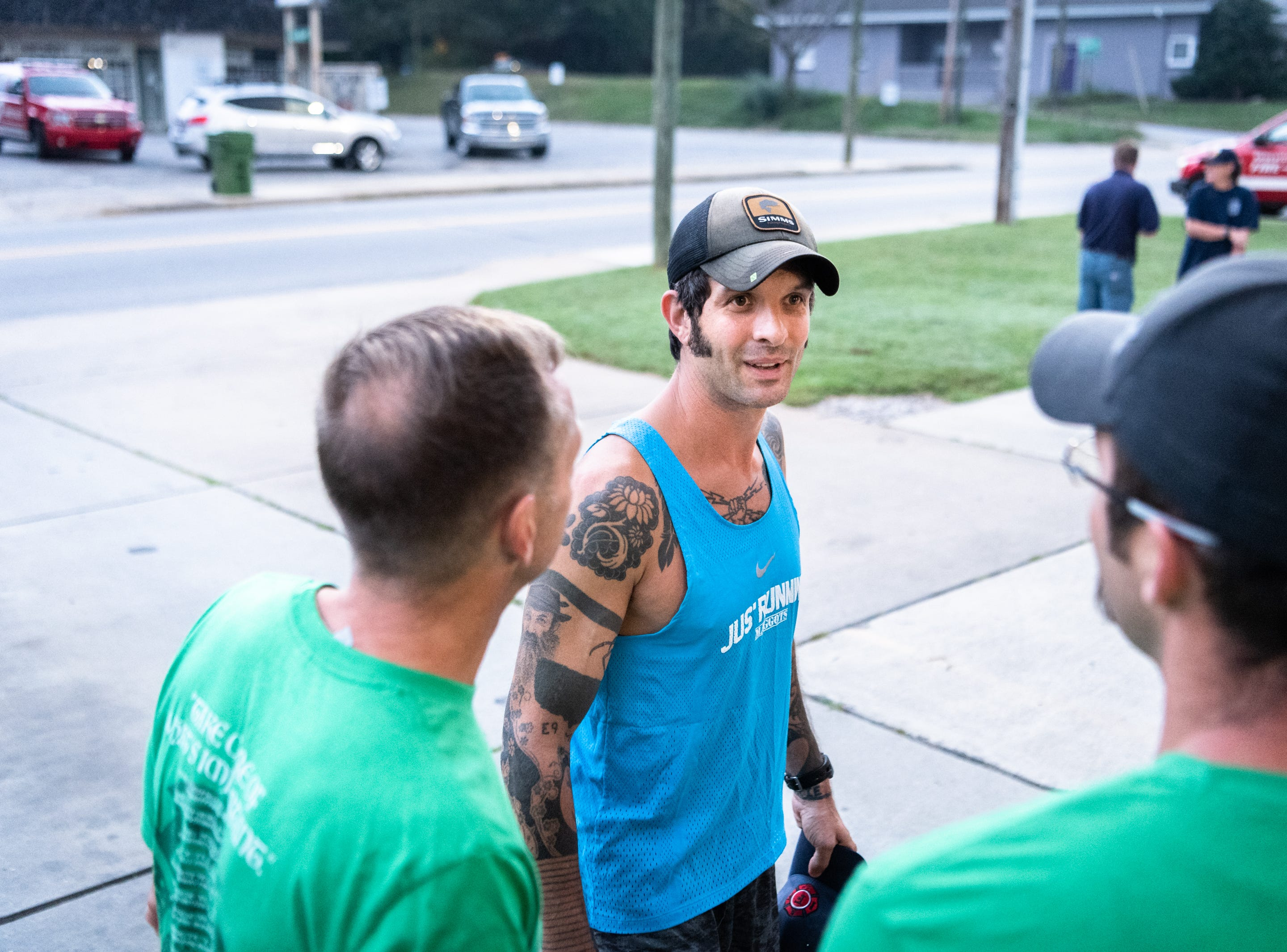 Mikey Riley, an Asheville firefighter, talks with other firefighters at station 6 on Haywood Road before beginning his 100k run to Ebbs Chapel and back Oct. 8, 2018. Riley is running one mile for every firefighter who has ever been diagnosed with cancer in an effort to raise awareness of firefighters' higher risk of cancer than the general population.