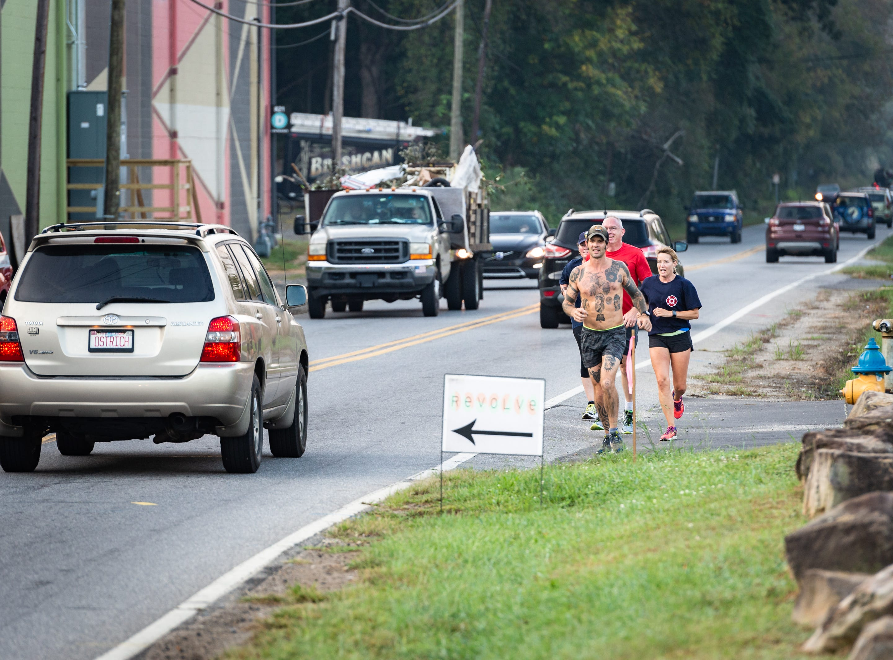 Mikey Riley, an Asheville firefighter, runs down Riverside Drive with Chief Joy Ponder, Captain Steve Wickam and Angela Wyricks at the beginning of his 100k to Ebbs Chapel and back Oct. 8, 2018. Riley is running one mile for every firefighter who has ever been diagnosed with cancer in an effort to raise awareness of firefighters' higher risk of cancer than the general population.