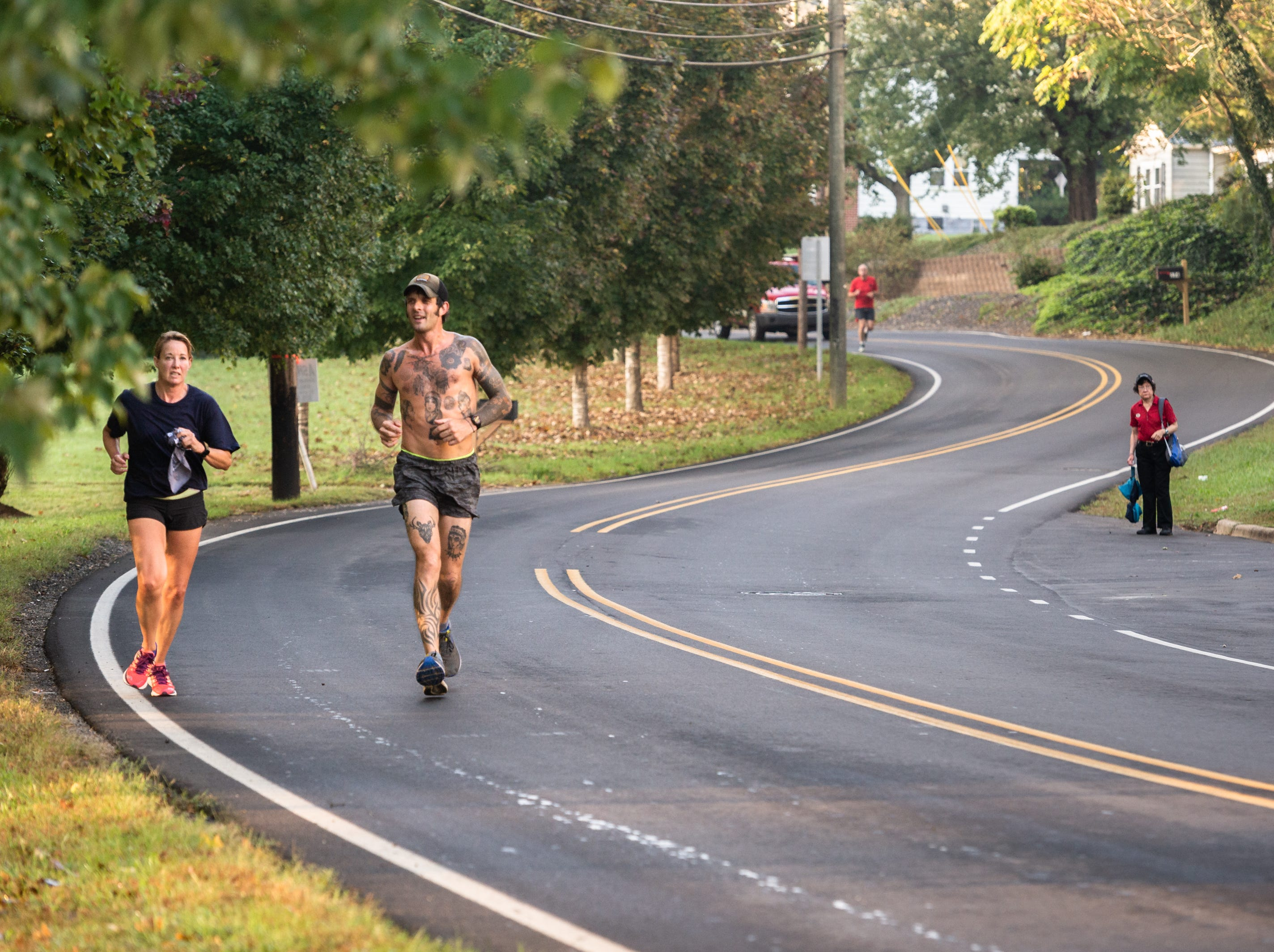 Mikey Riley, an Asheville firefighter, runs down Elkwood Avenue with Angela Wyricks and Captain Steve Wickam at the beginning of his 100k to Ebbs Chapel and back Oct. 8, 2018. Riley is running one mile for every firefighter who has ever been diagnosed with cancer in an effort to raise awareness of firefighters' higher risk of cancer than the general population. Riley began the run at station 6 on Haywood Road at 7:30 A.M and expects to arrive back around 7 P.M.