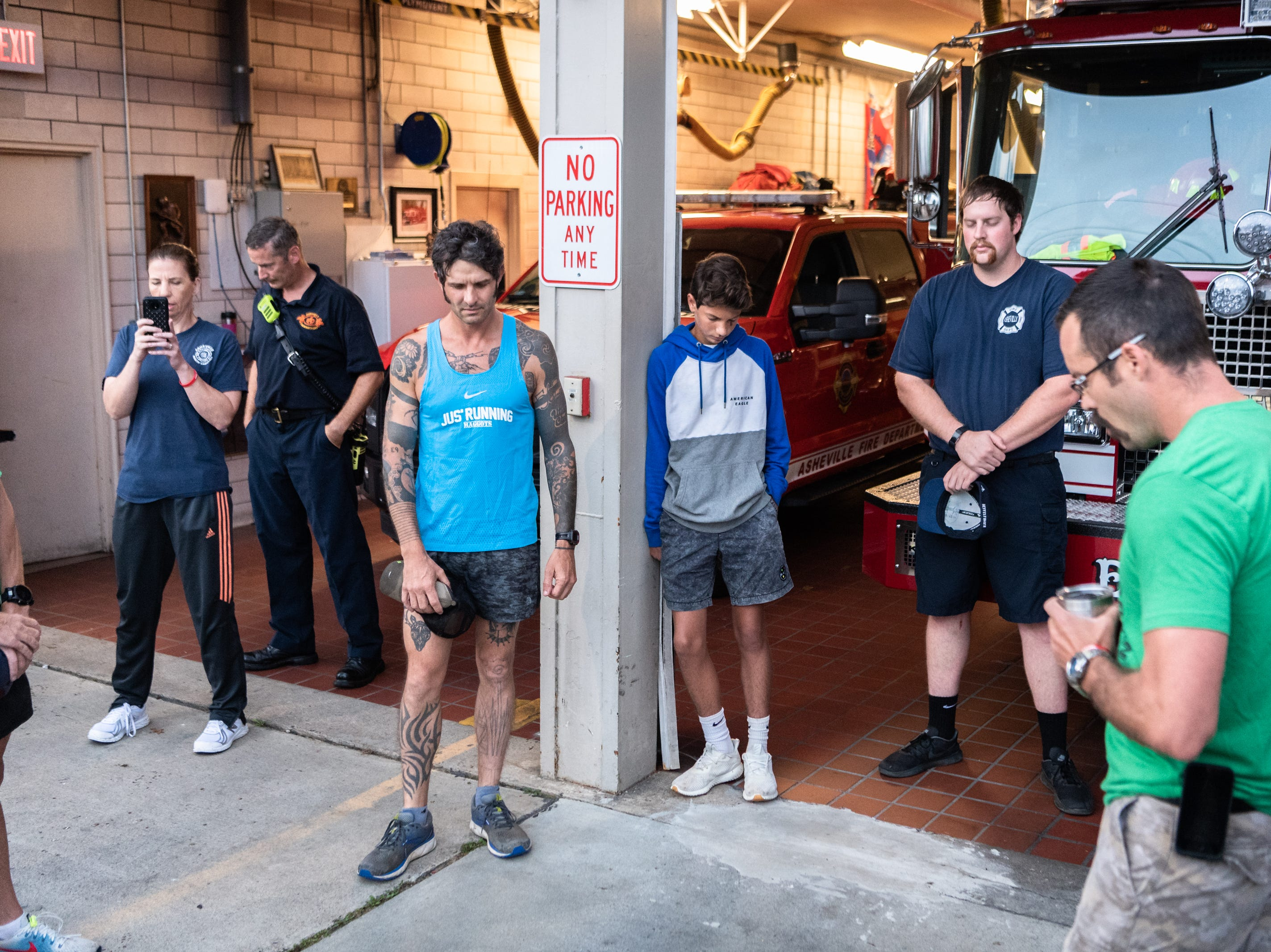 Mikey Riley, an Asheville firefighter, joins in prayer with other firefighters at station 6 on Haywood Road before beginning his 100k run to Ebbs Chapel and back Oct. 8, 2018. Riley is running one mile for every firefighter who has ever been diagnosed with cancer in an effort to raise awareness of firefighters' higher risk of cancer than the general population.