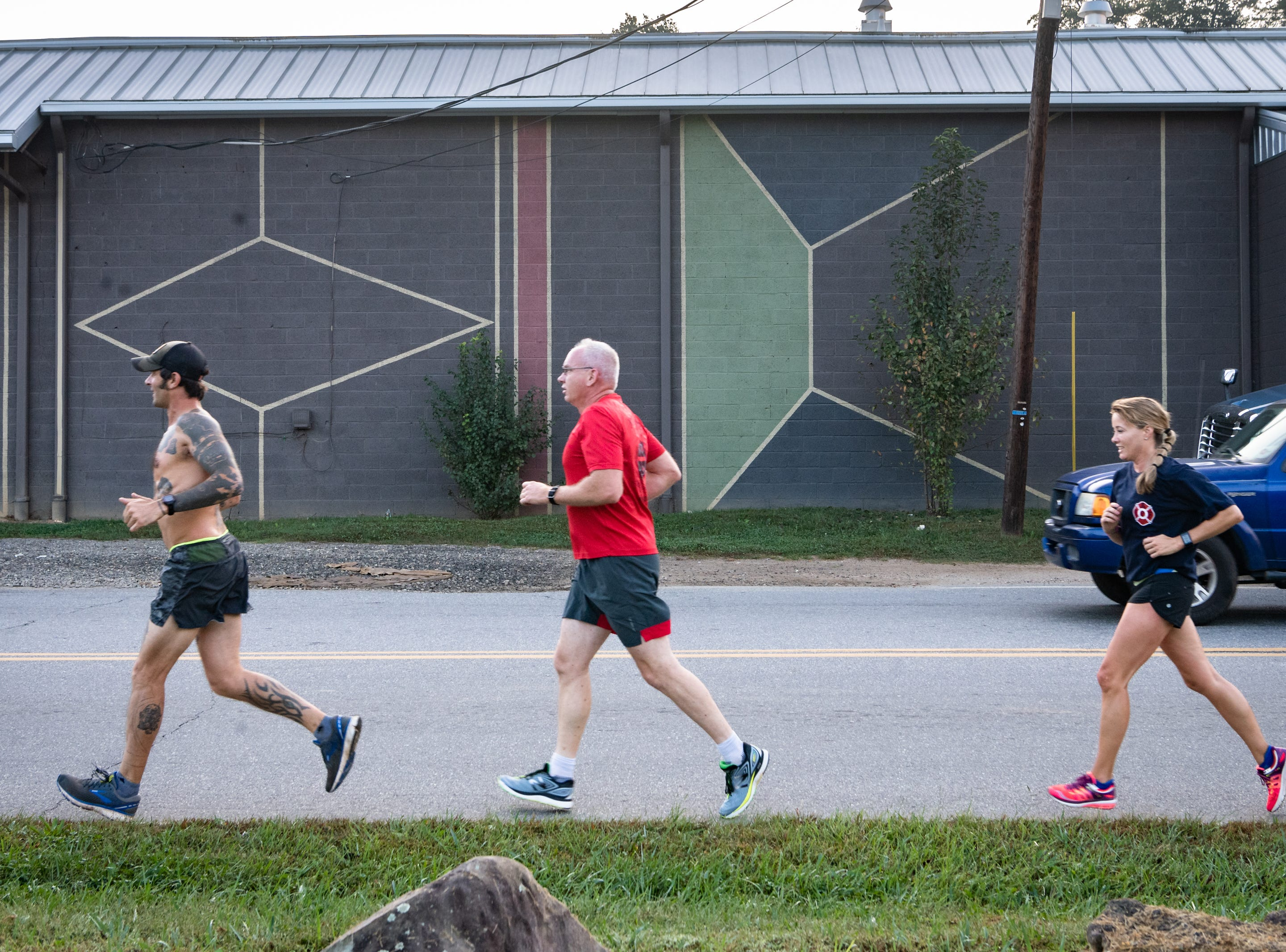 Mikey Riley, an Asheville firefighter, runs down Riverside Drive with Captain Steve Wickam and Angela Wyricks at the beginning of his 100k to Ebbs Chapel and back Oct. 8, 2018. Riley is running one mile for every firefighter who has ever been diagnosed with cancer in an effort to raise awareness of firefighters' higher risk of cancer than the general population and expects to arrive back at 7 P.M.