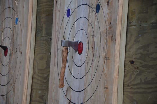 An ax hits the red for a bullseye during a BTL AXE league night on Thursday, October 4, 2018.