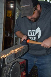 Jeremy Andrews sharpens an ax during a BTL AXE league night on Thursday, October 4, 2018.