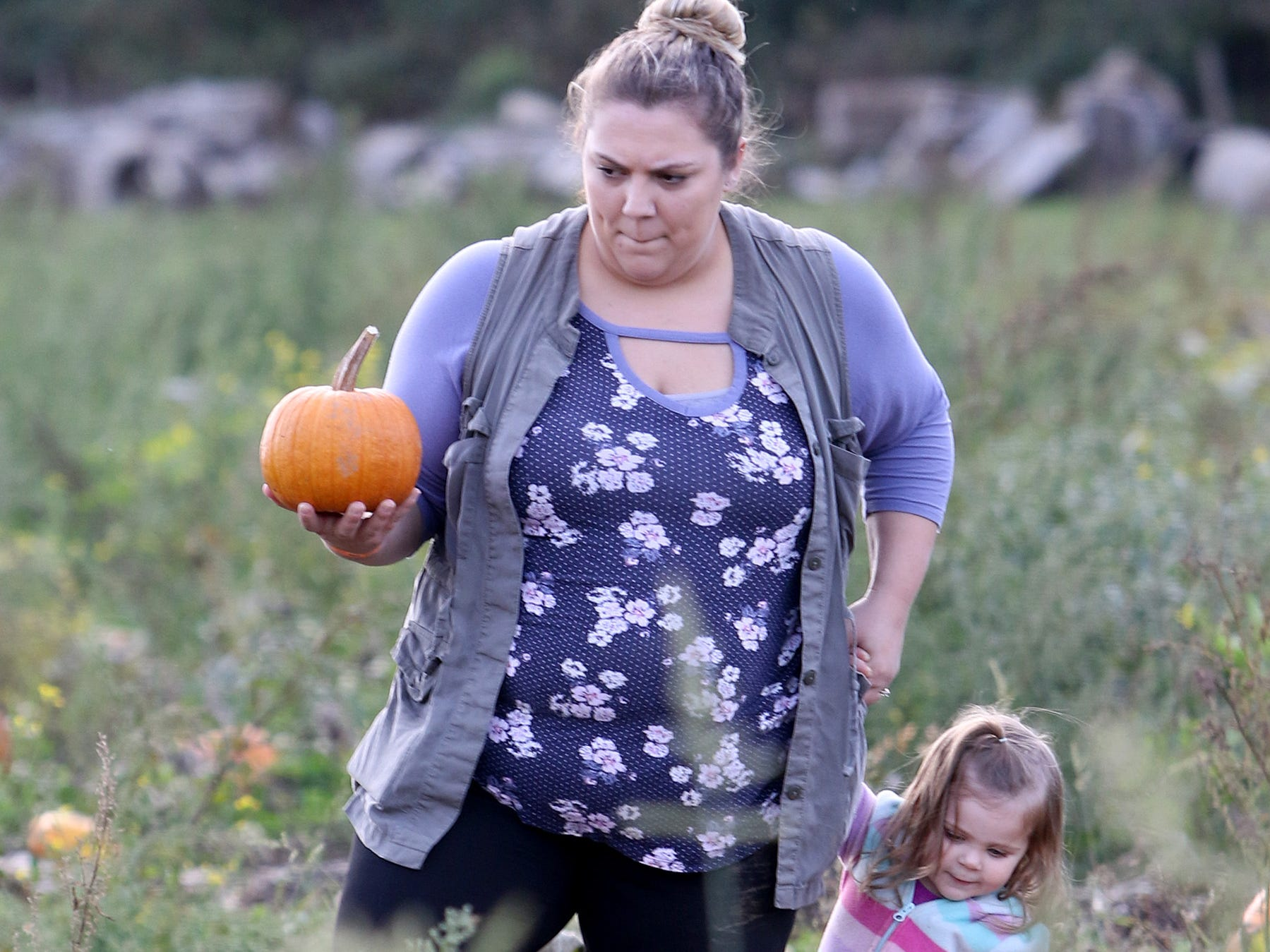 Danielle Contes, of Shelton, walks with her daughter Hailey through the Hunter Farms pumpkin patch.