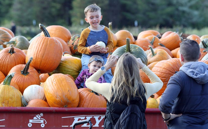 Kristen and Hayden Felt, of Silverdale, set their children Finley, 5 and Cora, 1,  on a pile of pumpkins for a photo at Hunter Farms near Union on October 6, 2018. Pumpkin Patch festivities run October 1-31 daily from 9:00am to 6:00pm.