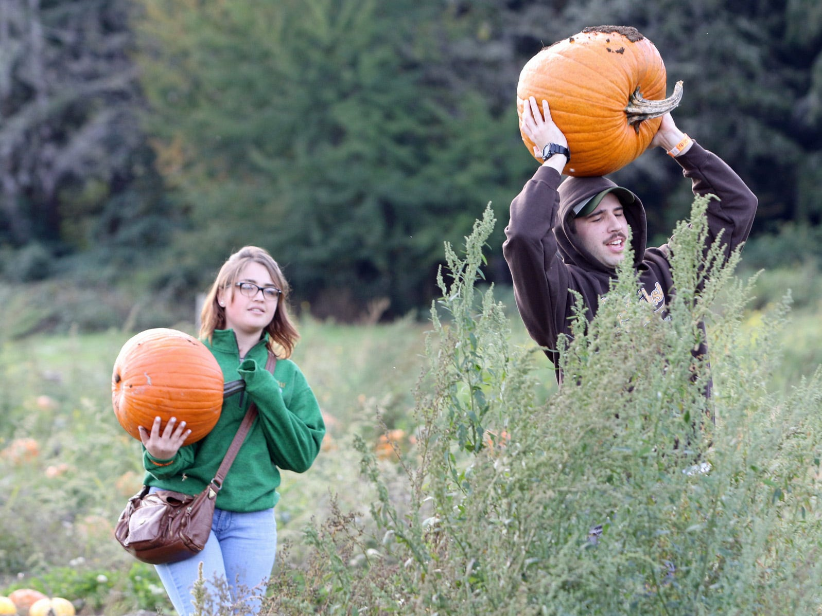 Asher and Samantha Fewell, of Seabeck, carry their pumpkins from the Hunter Farms pumpkin patch.