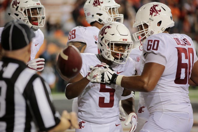 Washington State's Travell Harris (5) celebrates with teammate Andre Dillard (60) after scoring a touchdown during Saturday's win over Oregon State. The Cougars, expected to be in a rebuilding year, are 5-1 and on the verge of breaking into the AP Top 25.