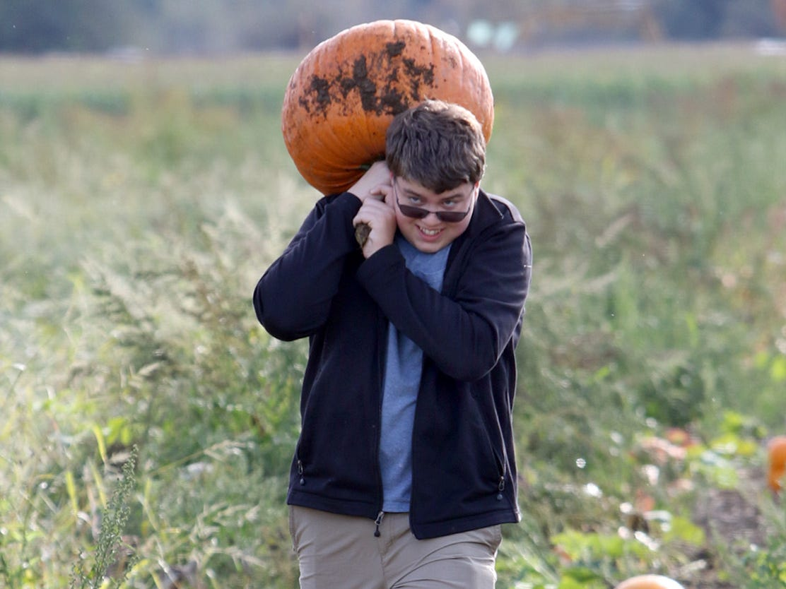 Ethan Karls, of Redmond, lugs his pumpkin from the field at Hunter Farms near Union on Sunday, October 7, 2018.