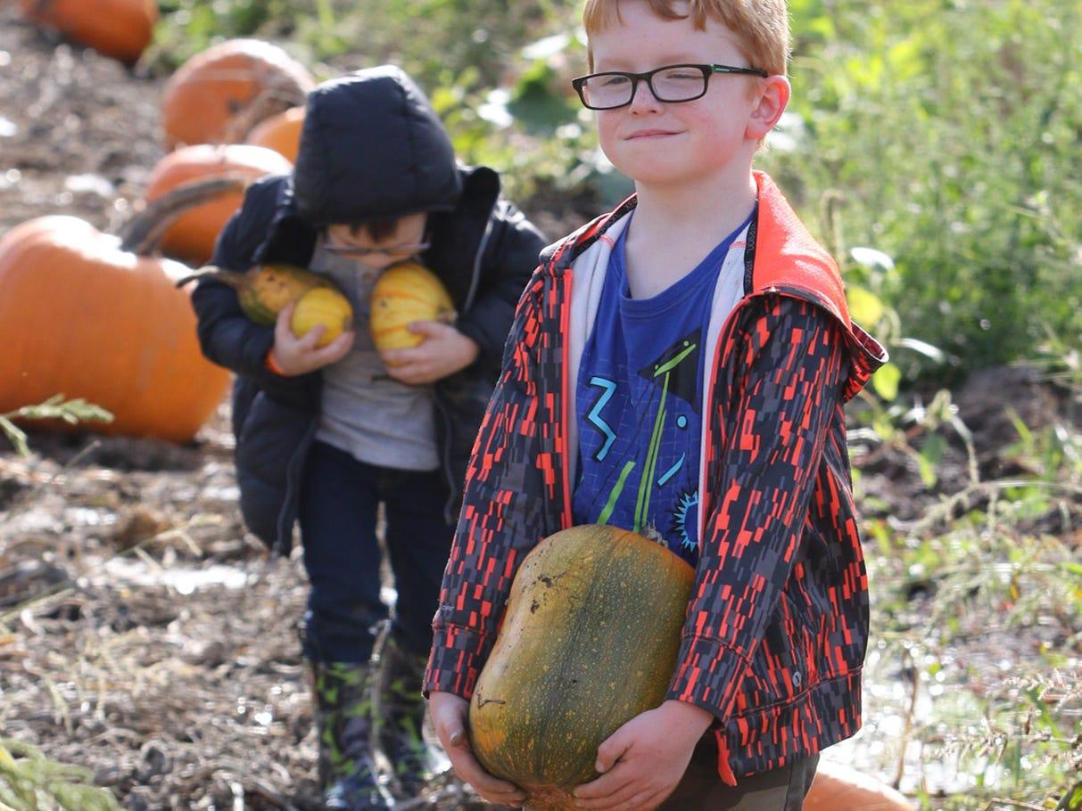 Wyatt Fogelman, 6 of Port Orchard, carries his pumpkin from the pumpkin patch.