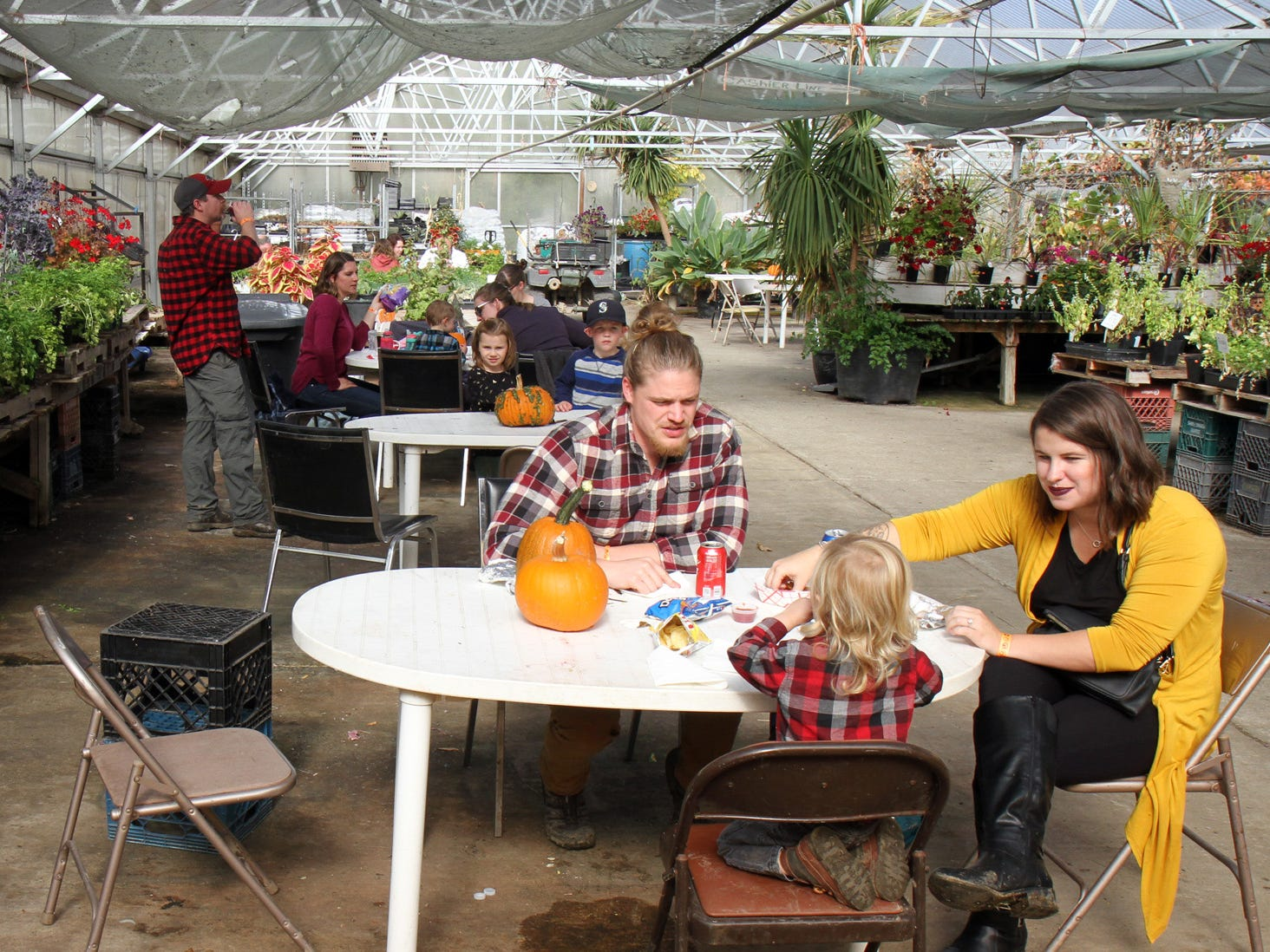 Sam and Derek Mellendorf, of Silverdale, enjoy a snack with their son Chase in the Hunter Farms green house.