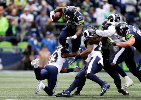 Seattle Seahawks running back Mike Davis (27) leaps over Los Angeles Rams strong safety John Johnson.