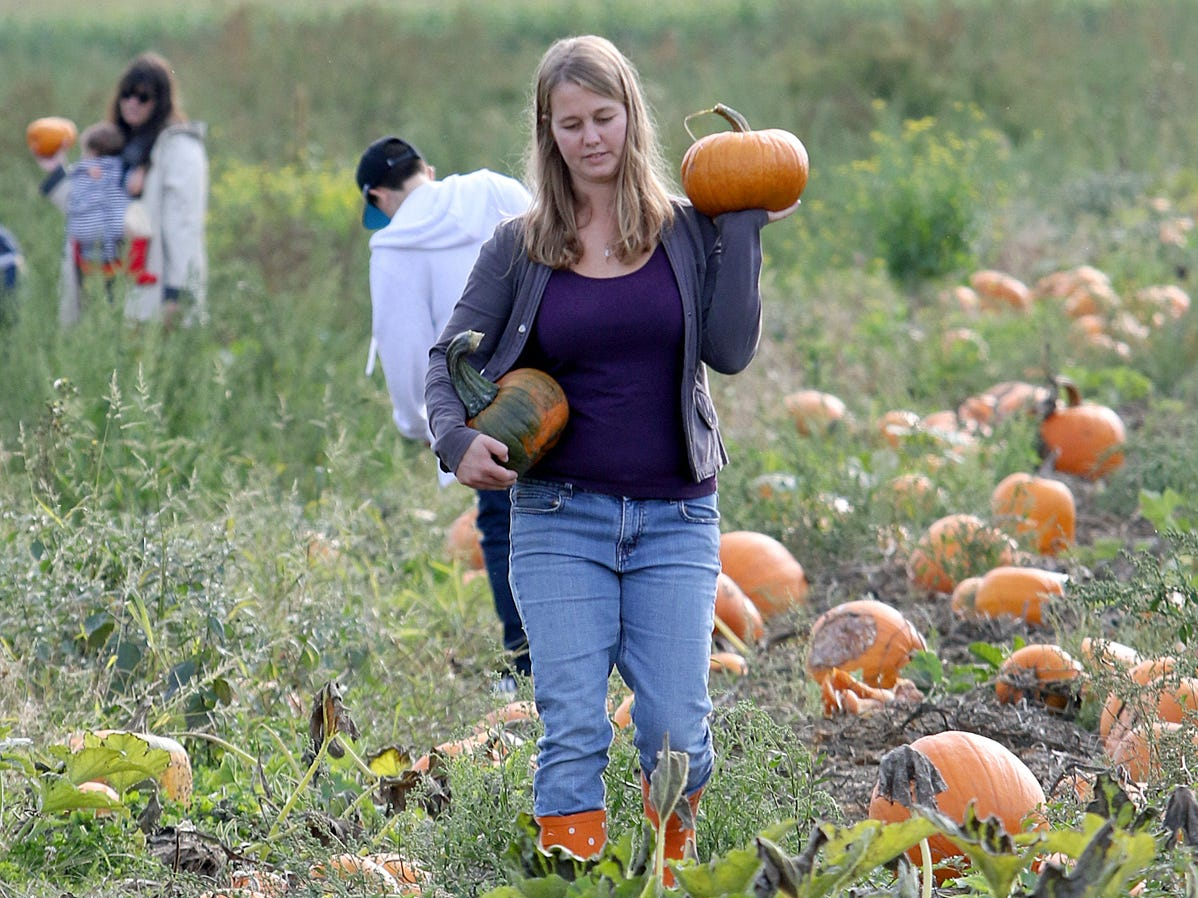 Melissa Dinius, of Gig Harbor, carries the pumpkins of her choice from the pumpkin patch at Hunter Farms.