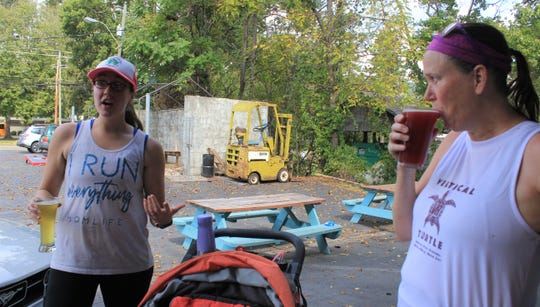 Katilyn Guyer, left, and Julia Moore drink beer at Lookout Brewing Co. after a Sunday run.
