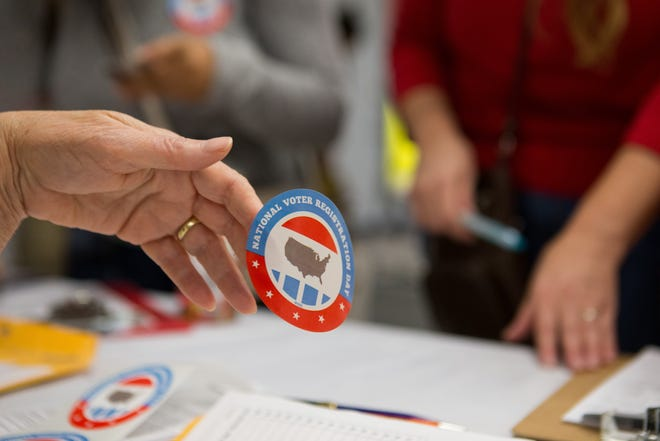 A member of the League of Women's Voters hands out a National Voter Registration Day sticker at Del Mar College on Tuesday, Sept. 27, 2016.