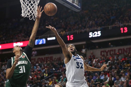 Minnesota's Karl-Anthony Towns shoots a lay-up while Milwaukee's John Henson defends during the preseason match-up between the Minnesota Timberwolves and the Milwaukee Bucks on Sunday, Oct. 7, 2018, in Hilton Coliseum in Ames, Iowa.