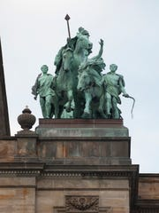 At the top of the building are a pair of copper-plated sculptures --  two goddesses astride four-horse chariots.