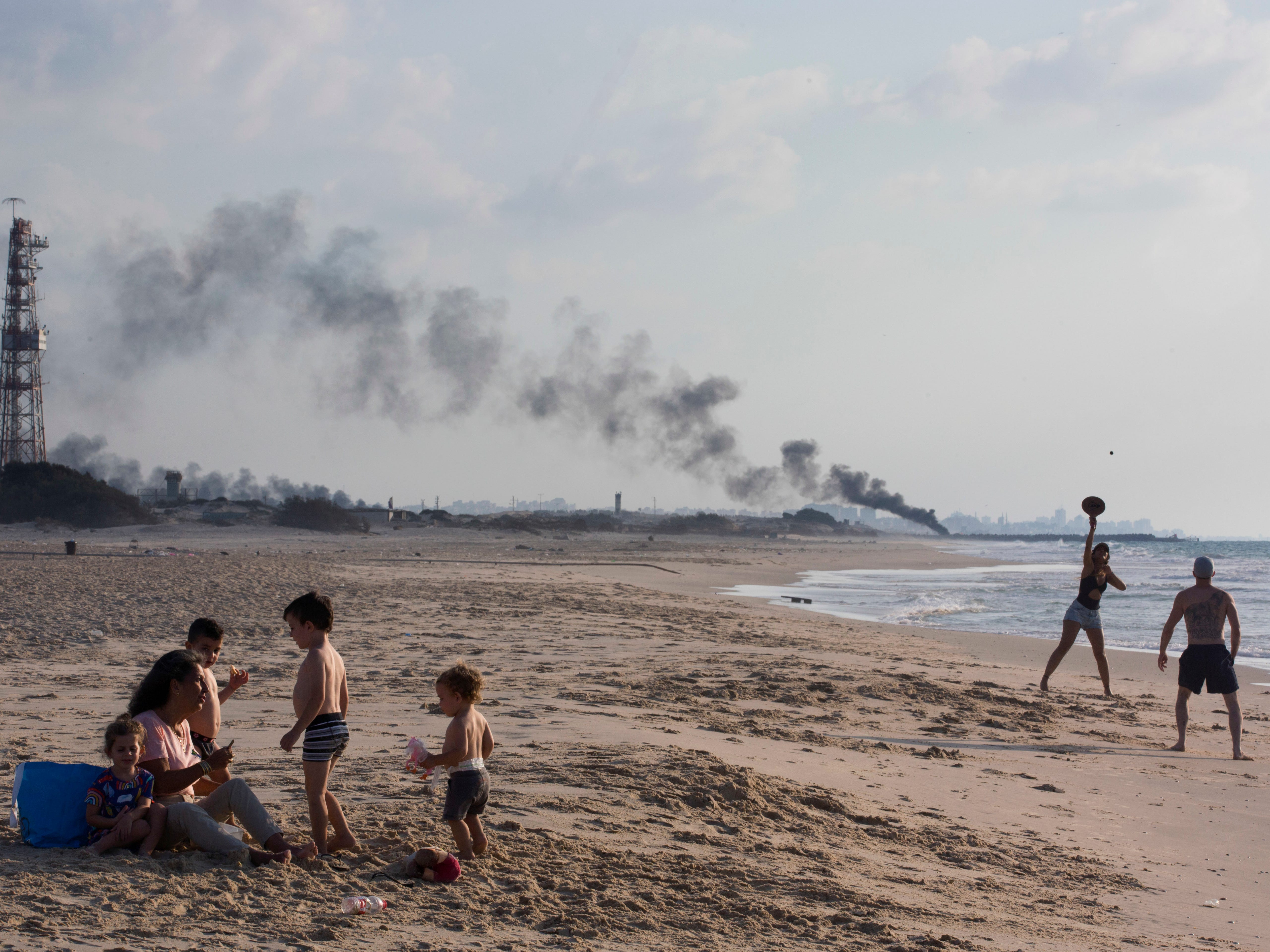 Israelis enjoy the day in Zikim beach, near kibbutz Zikim, on the Israel and Gaza border, as in the background black smoke rises from the tires set on fire by Palestinian protesters near Beit Lahiya, northern Gaza Strip, Monday, Oct. 8, 2018.