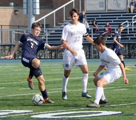 Patrick Finnerty of Elmira Notre Dame (7) tries to keep his balance with the ball as Delhi's Tristan Olson (22) and Preston Post defend during a boys soccer game Oct. 8, 2018 at Brewer Memorial Stadium.