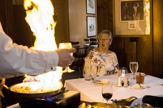 Mary Bryan reacts to the flames as Michael Steckler prepares the classic dish Steak Dianne tableside during her visit to the Kennel Club Thursday, Sept. 27, 2018. The private club is offering tableside preparations of many classic dishes and is also open to the public on Saturday evenings through the end of the year.