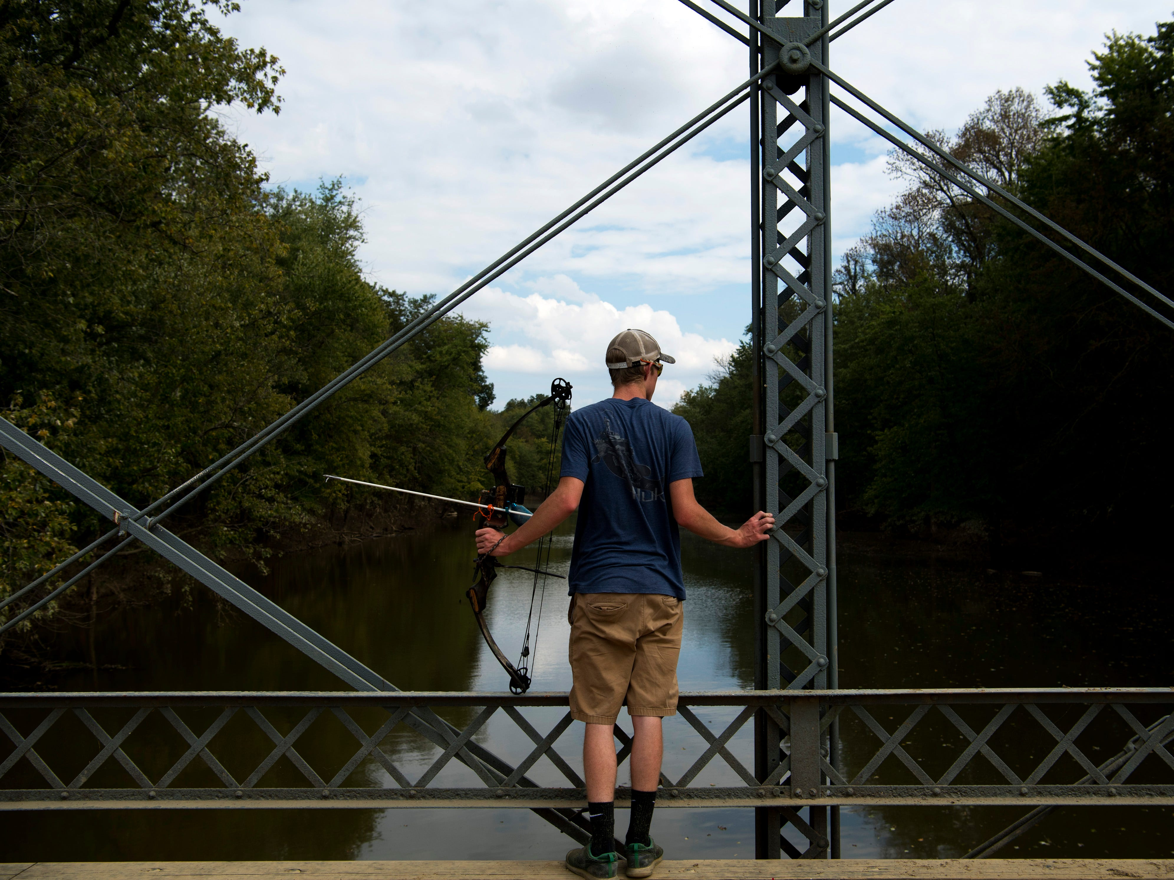 Jarrett Sandage, 17, a Boonville High School student, searches for carp with his bow and arrow above Little Pigeon Creek near Yankeetown, Ind., Monday afternoon. The bridge is a hot spot for local bow fishermen recently had about 30 archers perched atop the wood and steel structure.