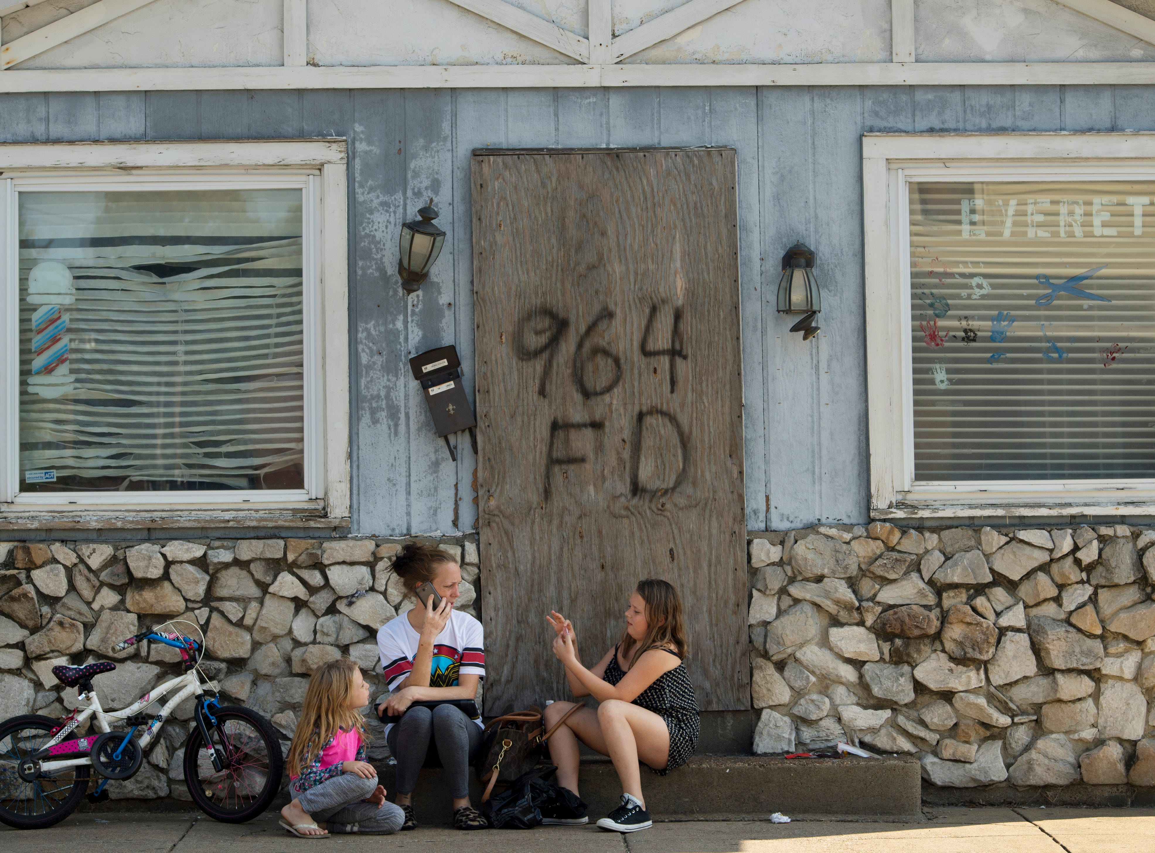 Hayden Effler, 7, left, Bryleigh Effler, 10, right, and their mom, Jessica Reeves, take a break from their walk in front of the old Everett Barber Shop in Evansville Monday morning. The kids are taking advantage of their spring break and won't have to go back to school until Thursday.