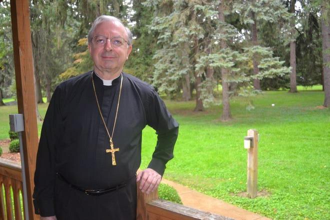 Bishop Joel Konzen stands on the porch of one of the hermitages on the grounds of Our Lady of the Pines in Fremont. Konzen stayed at the cabin during a recent visit to the area.