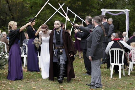 "Grady Magee and Sarah ""Star"" Marquardt walk under a lightsaber arch following their ""Star Wars""-influenced wedding ceremony Saturday in Shawano."