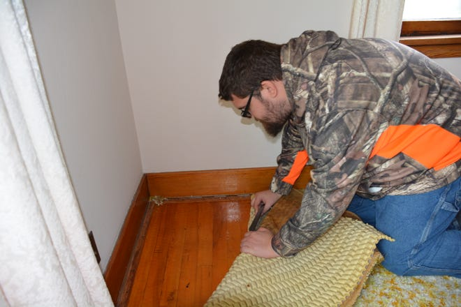 Frank Berger, 23, a client at Turning Point DC, examines the condition of the living room floor Oct. 3, 2018. The home in Sturgeon Bay was purchased by Turning Point DC to serve as a group home for adults with disabilities and will be renovated