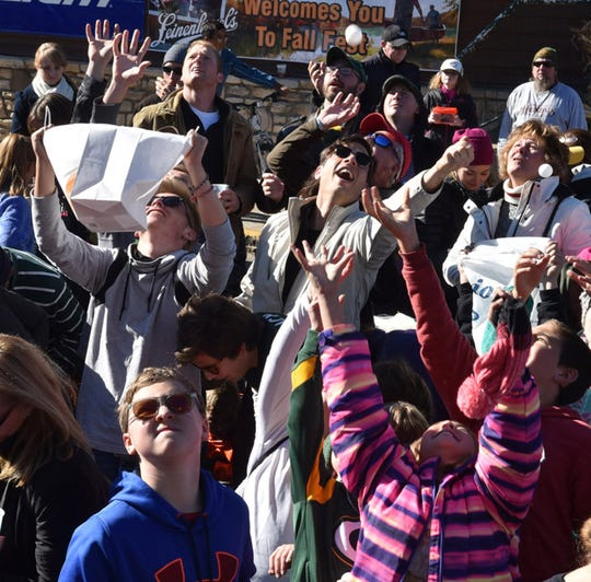 The crowd reaches for the heavens as they try to grab objects falling from the sky at the last Sister Bay Fall Fest pingpong ball drop, in 2015.
