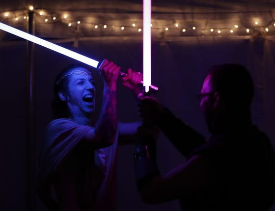 "Sarah ""Star"" Marquardt duels her new husband, Grady Magee, during the couple's ""Star Wars""-themed first dance after being married Saturday in Shawano."