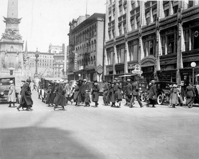 On a sunny, but cold, afternoon in February 1923, pedestrians scurried across Meridian Street in this midday view looking north from Washington Street. Proper winter attire included long, black coats and hats for everyone Ð men, women and children alike.