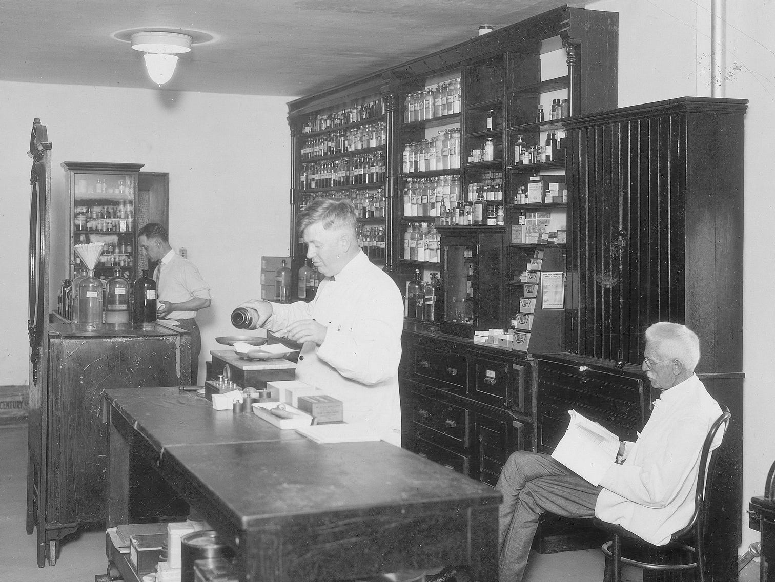 The drug store in the basement of the left wing of the City Hospital (now Wishard) in August 1924.  Druggist Walter Starrett, H. B. McCockley and J.E. Allen are shown.