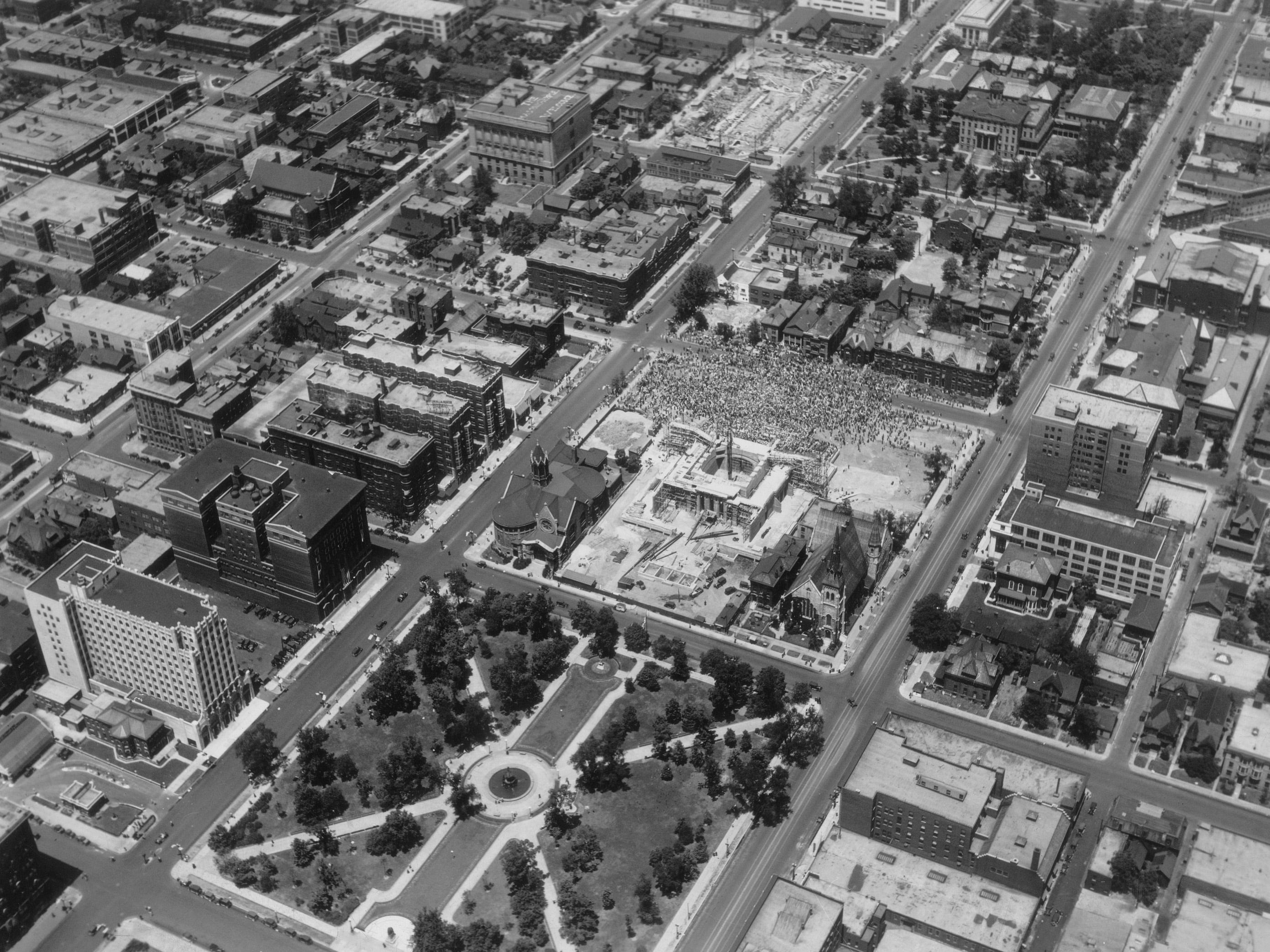 "Aerial of Indiana War Memorial and University Park. Crowd is gathered on north side of War memorial listening to John J. Pershing speak during the cornerstone ceremony on July 4, 1927, saying he was ""consecrating the edifice as a patriotic shrine""."