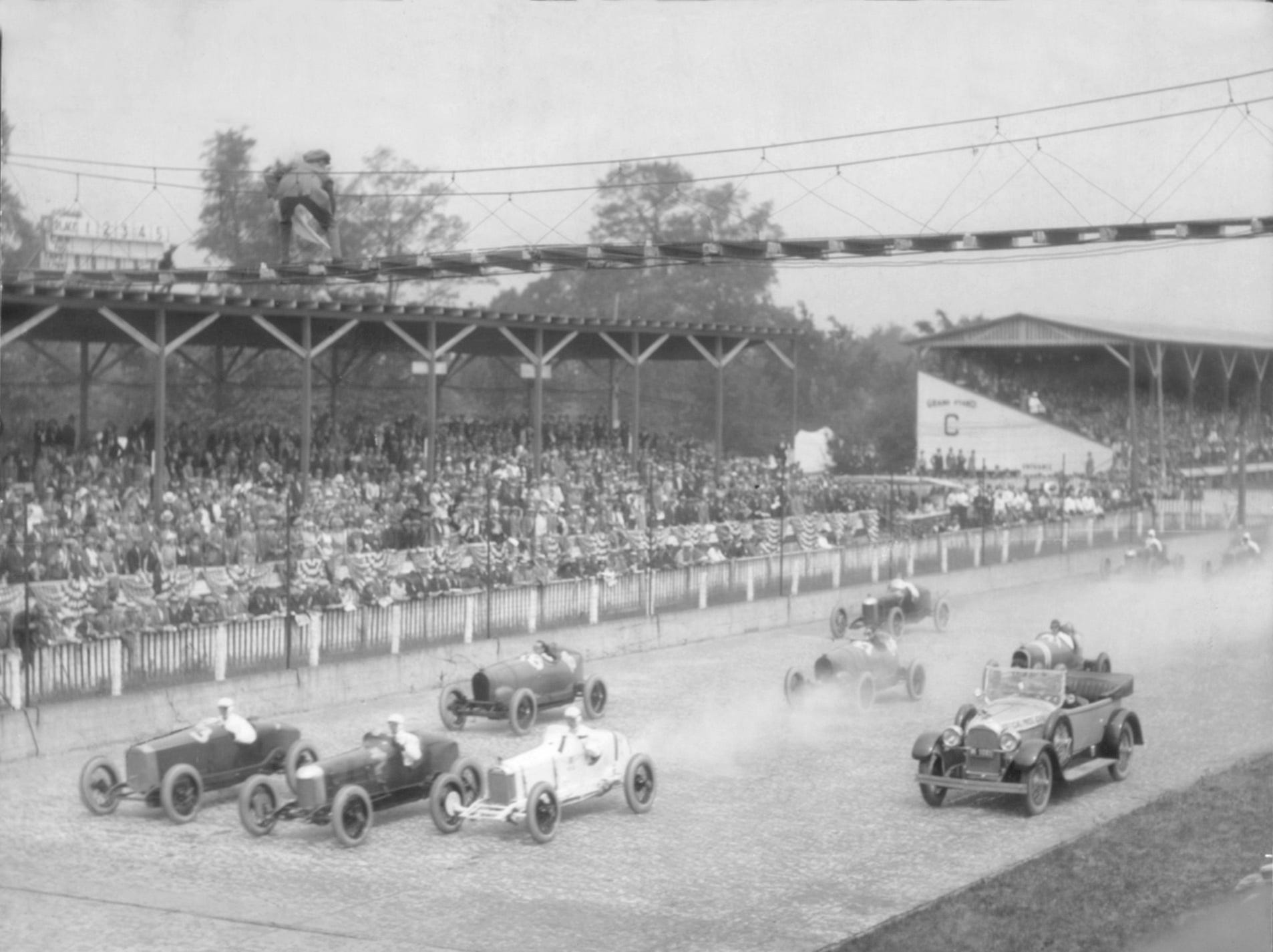 Fred Duesenberg, veteran racing car manufacturer, pulls the pace car to the side of the track as famous war aviator Eddie Rickenbacker (at top) waved the racers away for the flying start of the Indianapolis 500 at 10 a.m. on May 30, 1923. This was the last race where the starter stood on the footbridge strung across the track -- it was replaced the following year by a starter's stand at the side of the straightaway.