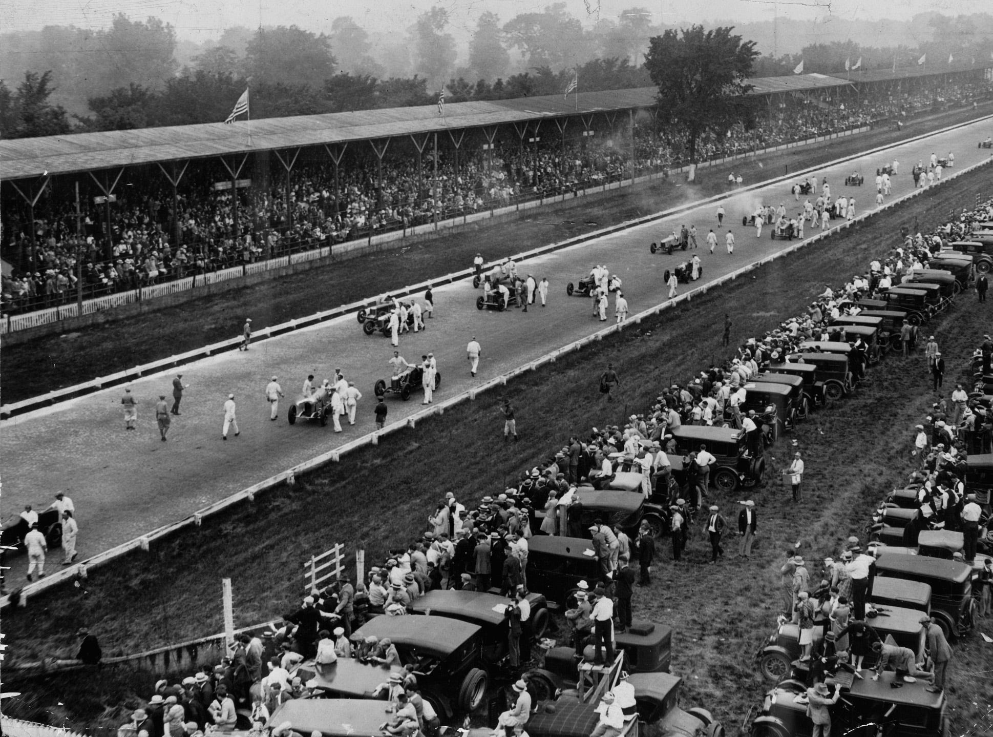]A record-breaking crowd filled the grandstands and swarmed around their automobiles parked trackside along the infield facing the main straightaway as the starting field was moved into position for the 1927 Indianapolis 500-Mile-Race.