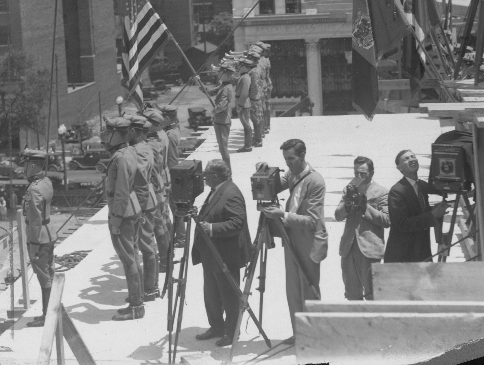 Photographers used bulky cameras on tripods to record ceremonies marking the cornerstone laying of the Indiana World War Memorial on July 4, 1927.  The color guard is facing north.