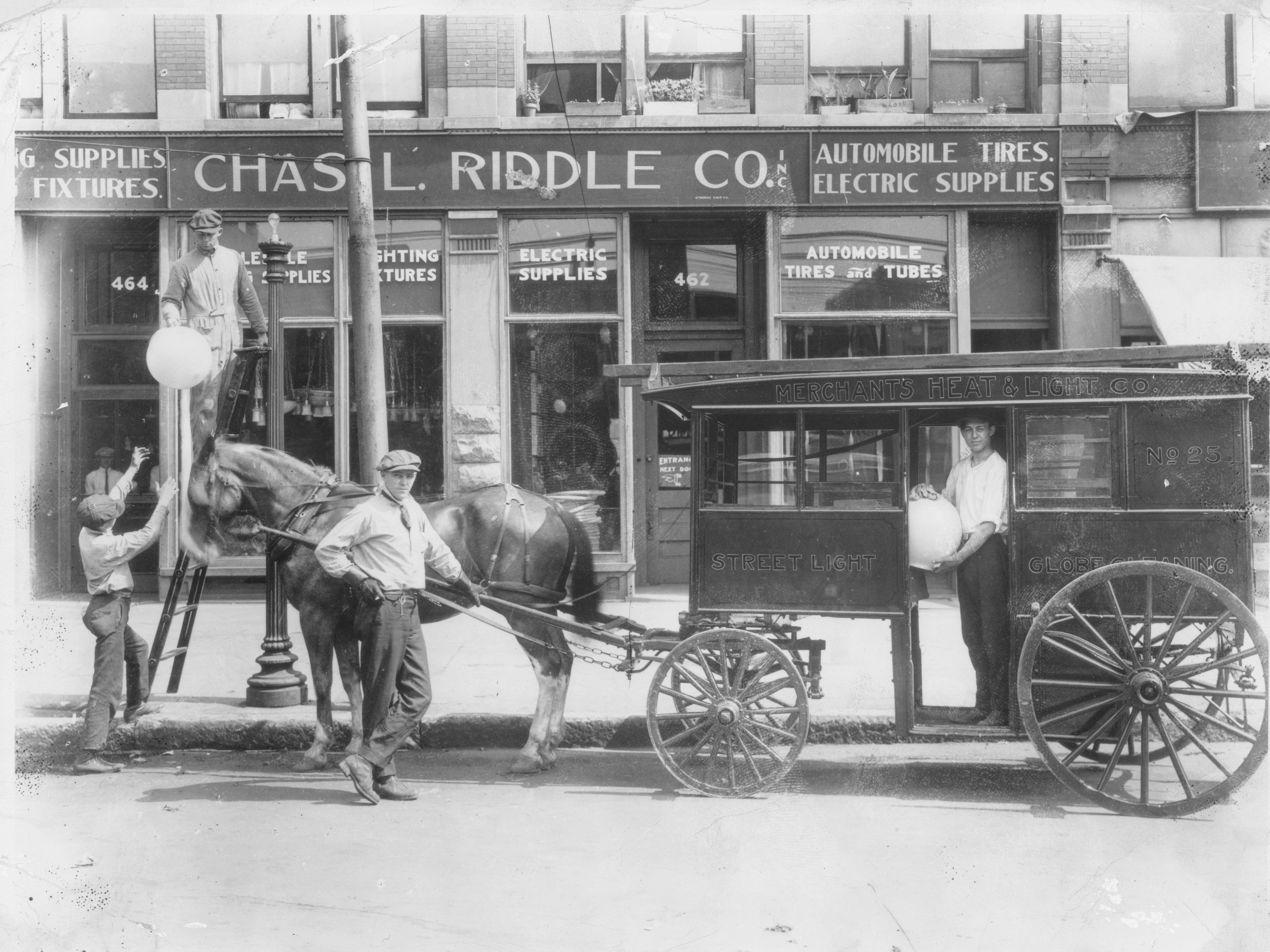 This horse drawn lighting patrol was still in existence in Indianapolis in 1921 when this photo was taken. In the background is the Chas. L. Riddle Co., Inc., which sold various supplies and fixtures, including automobile tires and electric lighting fixtures.