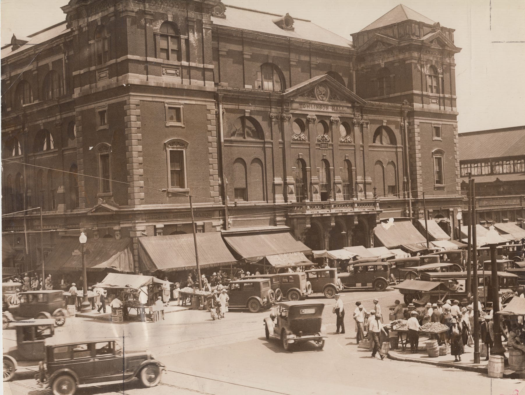 Tomlinson Hall served the city as a public meeting hall for more than 40 years. Truck farmers set up their stands at the farmer's market outside the hall on  July 7, 1927