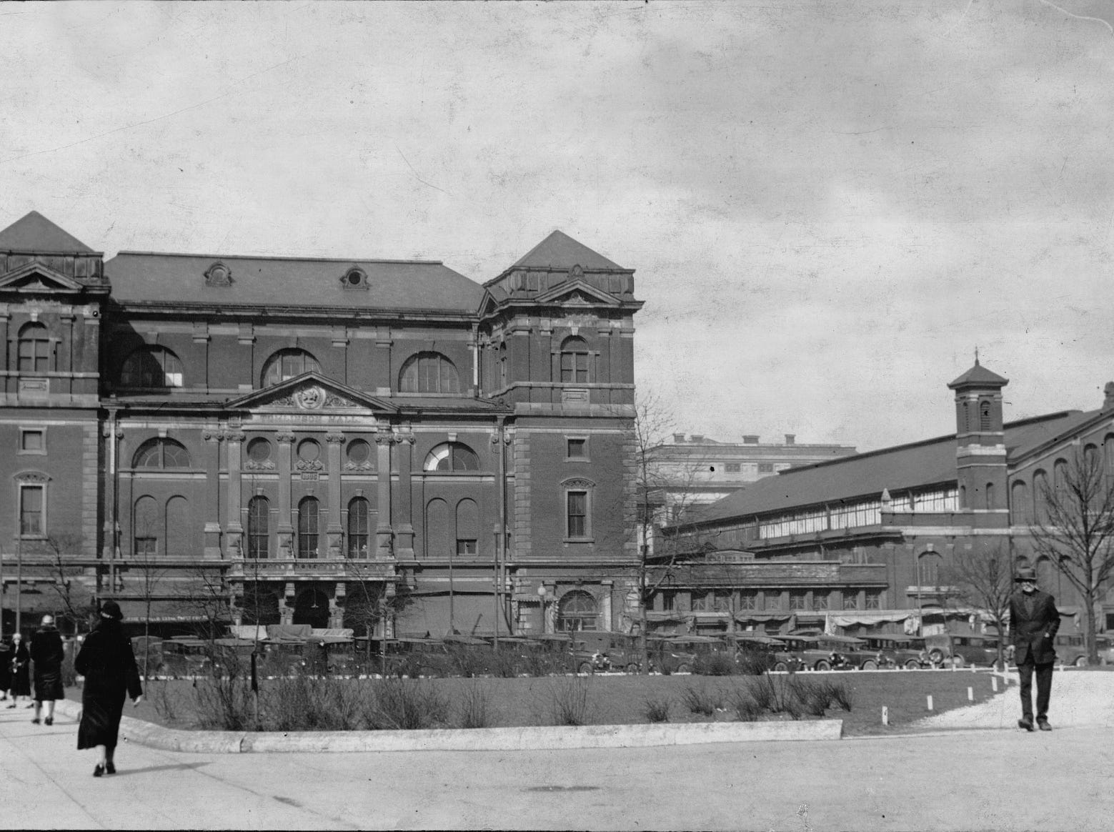 Indianapolis' Tomlinson Hall (left) had served the city as a public meeting hall for over 40 years when this picture was taken in the late 1920s. The view, looking north across the lawn of the old Marion County Courthouse, also shows the City Market at right. On the night of Jan. 30, 1958 the structure caught fire, illuminating the downtown area as flames climbed hundreds of feet into the air. The historic hall was razed six months later. A single doorway arch facing east is all that stands today in the market's courtyard (visible here in the lower right hand corner of the hall, where it attached to the City Market). Photo by unidentified Indianapolis News photographer, circa 1929
