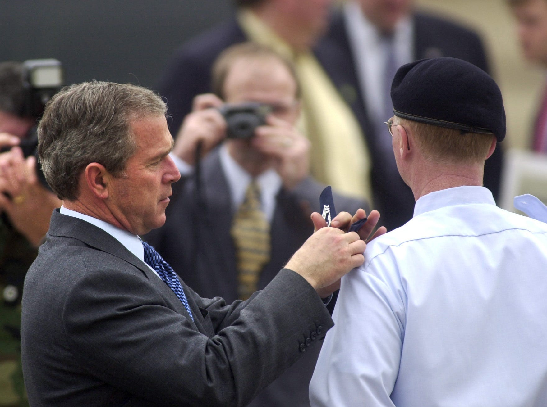 President George W. Bush pins new stripes on Chief Master Sgt. Terry Hickle Wednesday, Feb. 21, 2001, at McGhee Tyson Air National Guard Base. Hickle, the chief of security for the 134th Air Refueling Squadron, was promoted from senior master sergeant in a brief ceremony before Bush departed the airbase.