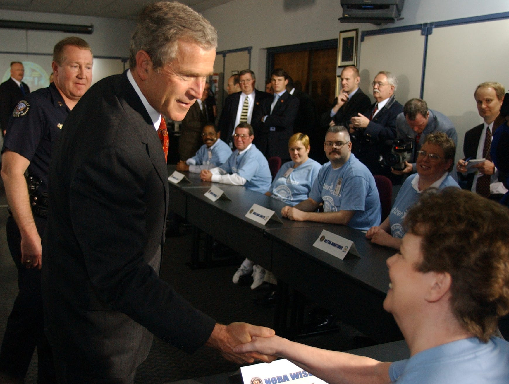 President George W. Bush shakes hands with Nora Wiser with the Citizens Corps as Knoxville Police Department Capt. Don Green escorts the President through the Moses Center Monday, April 8, 2002.