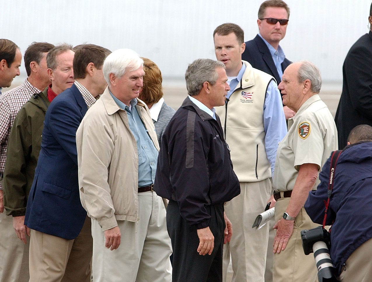 President George W. Bush talks to Bob Lochbaum, right,  a volunteer with the Adopt-a-Trail program in the Great Smoky Mountains National Park,  Friday, April 22, 2005, at McGhee Tyson Air National Guard Base. Bush planned to celebrate Earth Day in Cades Cove, a visit which was cut short by bad weather.