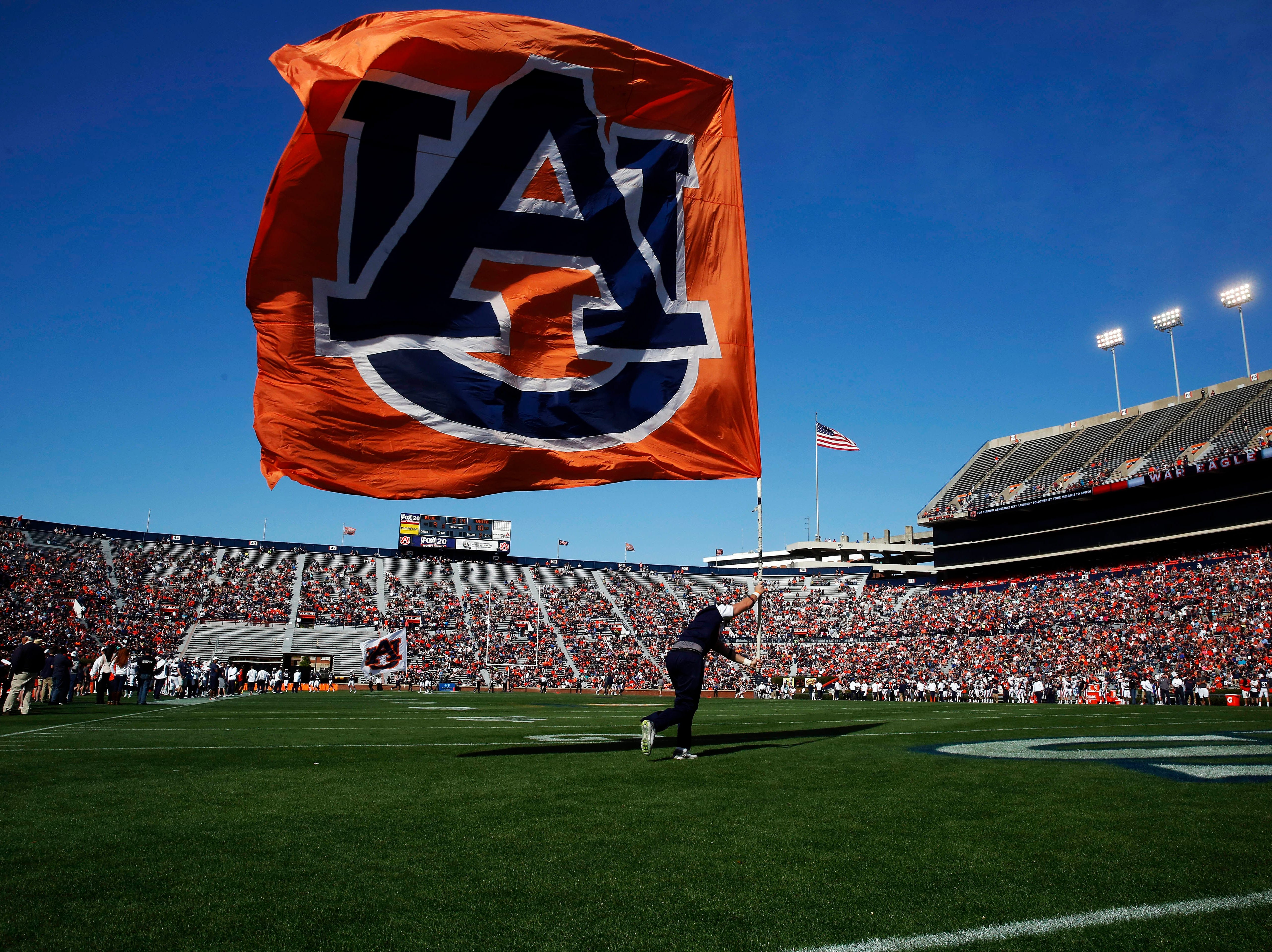 After Auburn scores a cheerleader carries a flag across the end zone in celebration in the first half during a spring NCAA college football game Saturday, April 9, 2016, in Auburn, Ala.