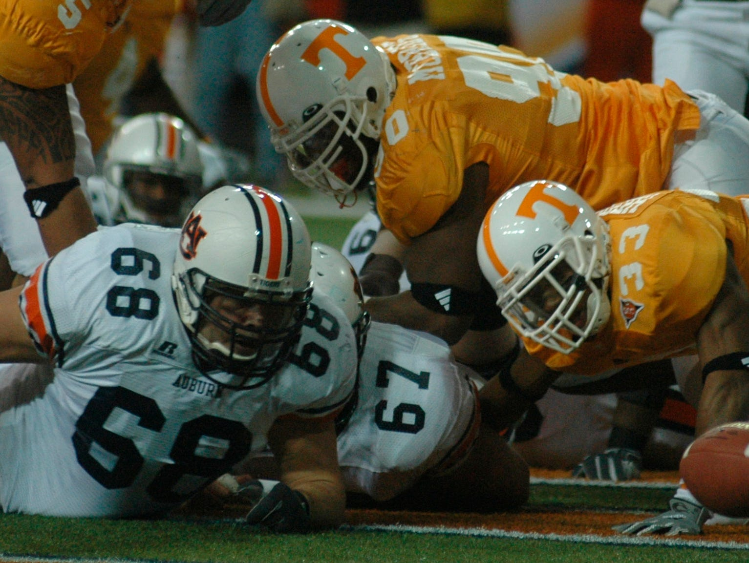 Tennessee cornerback Jonathan Hefney (33) eyes a goal line fumble by Auburn running back Carnell Williams during the Southeastern Conference championship game Saturday in Atlanta. Auburn's Cole Bennett recovered the ball in the end zone to score the Tiger's first touchdown. Auburn's Danny Lindsey, left, and Tennessee's Turk McBride, top, were in on the play. 12/04/2004