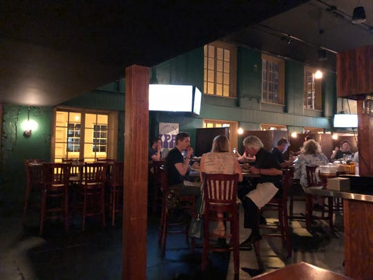 The dining room at Blackhorse Pub and Brewery features over-sized wooden booths and vintage whiskey barrel side tables.